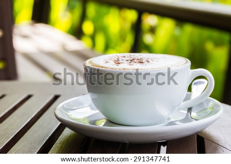 Cappuccino or latte coffee on wooden table in the cafe. - stock photo