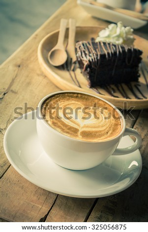 Cappuccino or latte coffee on wooden table. Vintage color tone. - stock photo