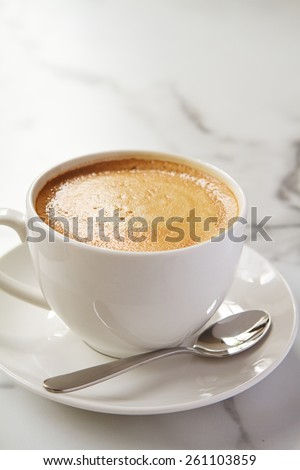 Cappuccino or latte milk coffee in white cup and saucer on a marble table - stock photo