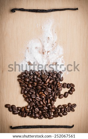 Cappuccino time. Roasted coffee beans placed in shape of cup with white froth vanilla pods on wooden surface background - stock photo