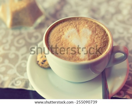 Cappuccino with a heart shape / Vintage style photo with costum white balance, and color filters effects - stock photo