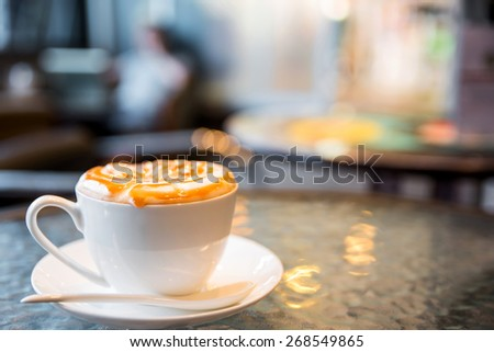 Cappuccino with blur coffee shop background - stock photo