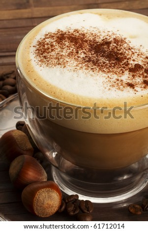 cappuccino with chocolate powder on milk froth and hazelnuts on wooden background - stock photo