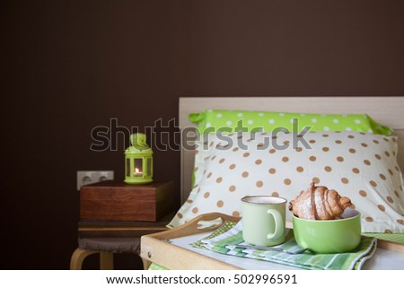 Cappuccino with cinnamon and croissant on a tray stand. Knitted fabric and skeins of white and beige yarn lie in a white basket. Green sheet with white polka dots. Two double bed. Brown wall.