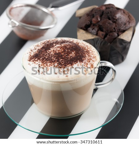 Cappuccino with cocoa and chocolate muffin. - stock photo