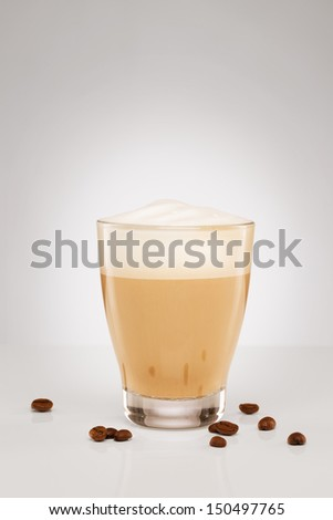 cappuccino with milk foam in a small glass with coffee beans on grey background - stock photo