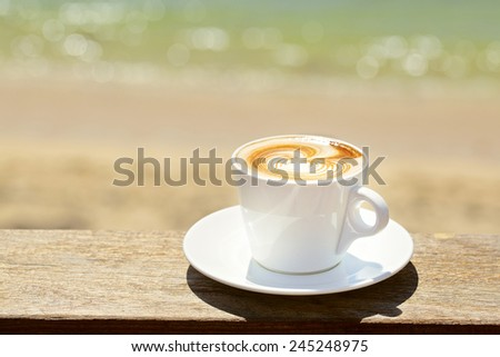 Cappuchino or latte coffe in a white cup  with heart shaped foam on wooden board with ocean on the background - stock photo