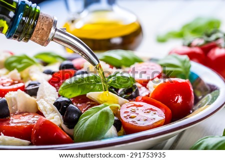Caprese. Caprese salad. Italian salad. Mediterranean salad. Italian cuisine. Mediterranean cuisine. Tomato mozzarella basil leaves black olives and olive oil on wooden table. Recipe - Ingredients - stock photo
