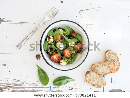 Caprese salad and chiabatta slices. Cherry-tomatoes, baby spinach and mozzarella in metal bowl with pesto dressing on rustic white wooden backdrop, top view, horizontal - stock photo