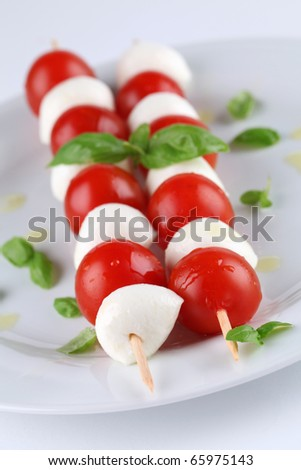 Caprese salad. Cherry tomatoes and mozzarella on skewers, garnished with basil leaves and olive oil - stock photo