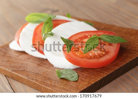 caprese salad made on wooden cutting board