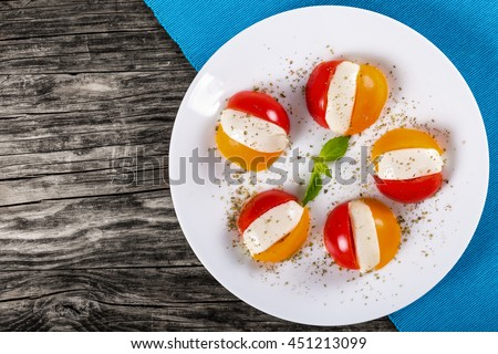 Caprese salad of tomatoes and mozzarella cheese, sprinkled with mixture of dried Italian herbs, decorated with basil leaves on white plate, view from above, blank space left - stock photo