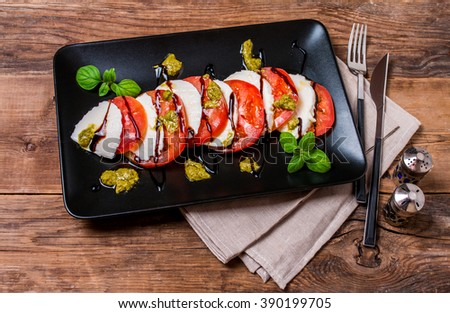 Caprese Salad on black plate - Salad with Tomatoes, Mozzarella Cheese, Basil and Balsamic. Salad Dressing with Pesto Sauce, top view - stock photo