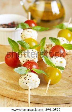 Caprese salad on wooden sticks - stock photo