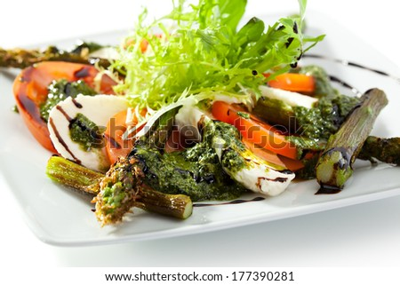 Caprese Salad - Salad with Tomatoes, Mozzarella Cheese, Asparagus, Balsamic. Salad Dressing with Pesto Sauce - stock photo