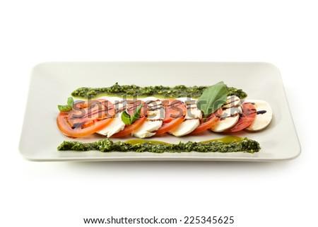 Caprese Salad - Salad with Tomatoes, Mozzarella Cheese, Balsamic Salad Dressing and Pesto Sauce - stock photo