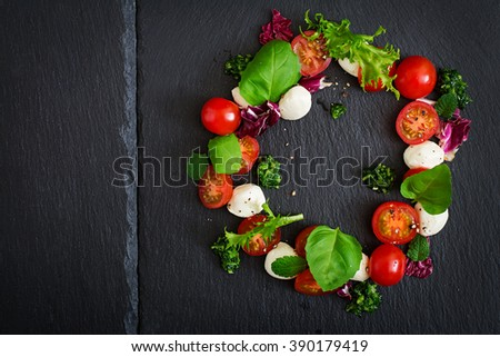 Caprese salad tomato and mozzarella with basil and herbs oon black background. Top view - stock photo