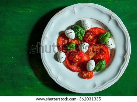 Caprese salad with baby mozzarella from above - stock photo