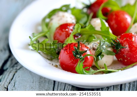 Caprese salad with fresh arugula leaves, mozzarella balls and tomatoes