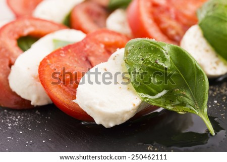 Caprese salad with mozzarella, tomato, basil and balsamic vinegar arranged on black plate  - stock photo