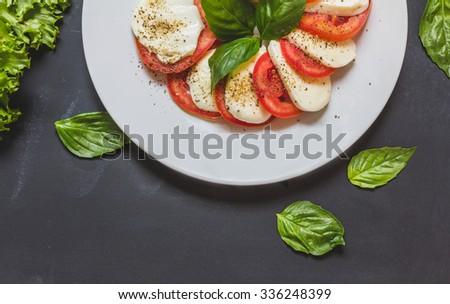 Caprese salad with mozzarella, tomato, basil on white plate. Top view on black background - stock photo