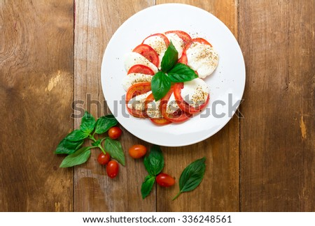 Caprese salad with mozzarella, tomato, basil on white plate. Top view on wood background - stock photo