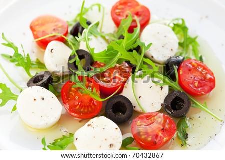 Caprese salad with mozzarella, tomatoes and black olive - stock photo