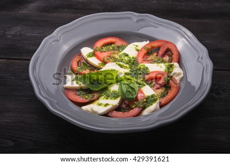 caprese salad with tomato and mozzarella on black wood table