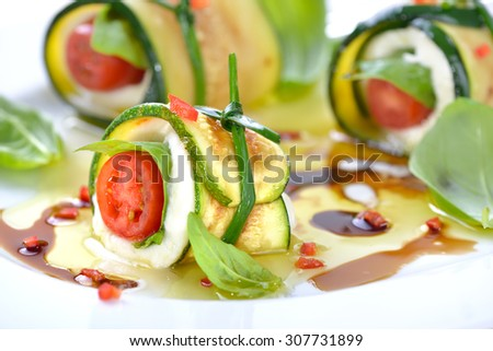 Caprese wrapped with fried zucchini slices, tied and knot with chives, marinated with olive oil and balsamic vinegar - stock photo