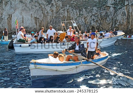 CAPRI, ITALY - OCTOBER 10 2014: School children and tourists in boats waiting to enter the famous Blue Grotto on the island of Capri. The rowboats are small enough for the narrow entrance to the cave. - stock photo