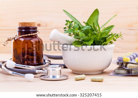 Capsule of herbal medicine alternative healthy care with stethoscope on wooden background. - stock photo