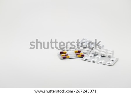Capsules and pills packed in blisters, isolated on white - stock photo