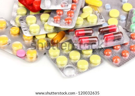 Capsules and pills packed in blisters isolated on white close-up - stock photo