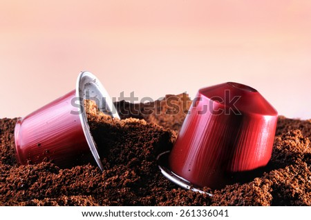 capsules for espresso coffee machine on heap of ground coffee and brown isolated background - stock photo