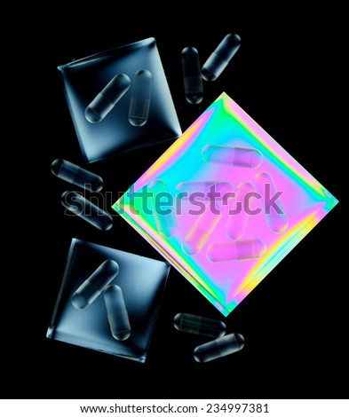 Capsules for medicines on colorful, graphic background of geometric shapes. Black background. - stock photo