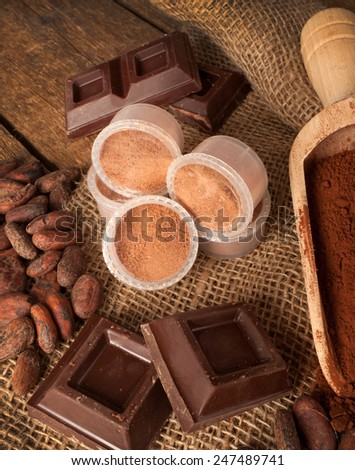 Capsules of chocolate with cocoa powder, cocoa beans and pieces of chocolate.