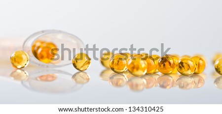 Capsules of fish oil spilled out open container - stock photo