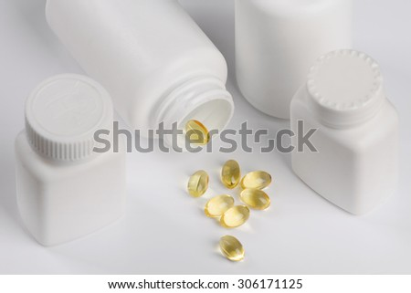 Capsules of fish oil spilled out open container on light background. Several bottles - stock photo