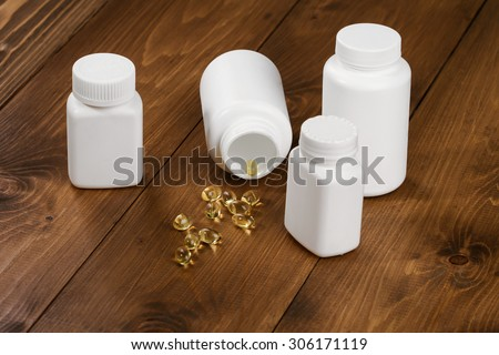 Capsules of fish oil spilled out open container on wooden table. Several bottles - stock photo