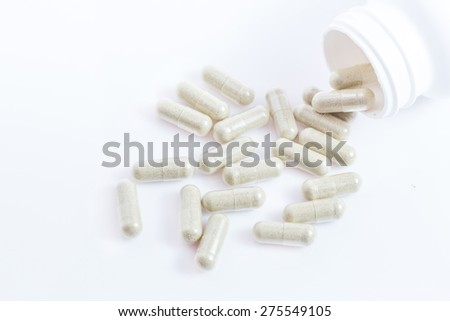 Capsules of green herbal supplement product isolated on white background - stock photo