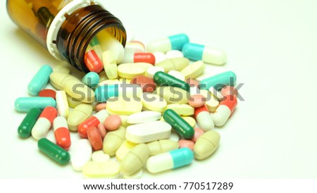 Capsules, pills, tablets on white table, top view.