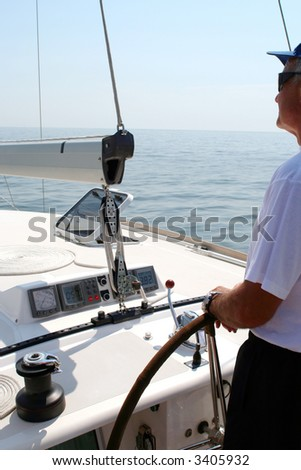 Captain beyond the yacht steering directing into the sea - stock photo