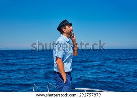 Captain cap sailor man talking mobile phone in boat sailing in the ocean sea - stock photo