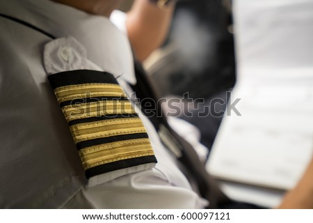 Captain in the aircraft cockpit writing a report after flight. Focusing on his pilot epaulets.