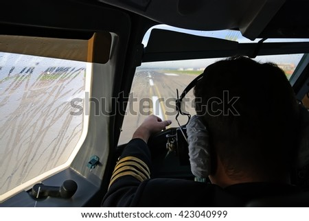 Captain is getting ready for takeoff while an aircraft lining up the runway, cockpit interior view - stock photo