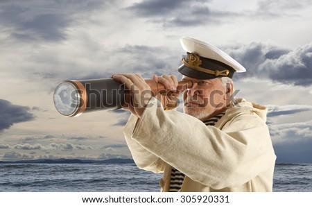 Captain looks through a telescope - stock photo