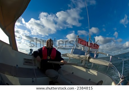 Captain of sailing yacht at the helm