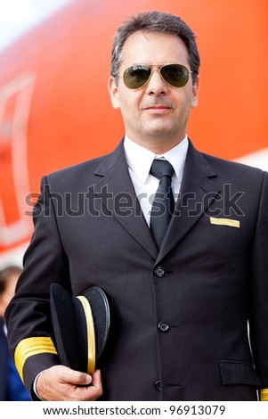 Captain pilot at the airport wearing sunglasses and holding hat - stock photo