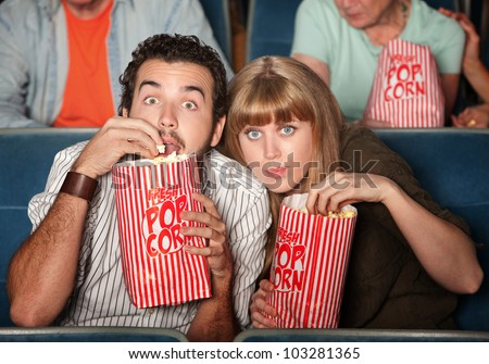 Captivated couple  with popcorn bags in a theater - stock photo