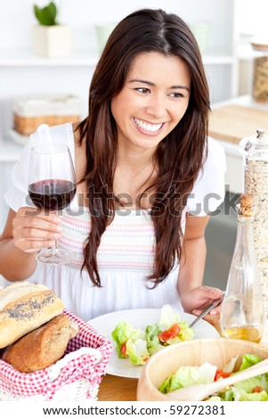 Captivating asian woman holding a wineglass eating a salad at home in the kitchen - stock photo